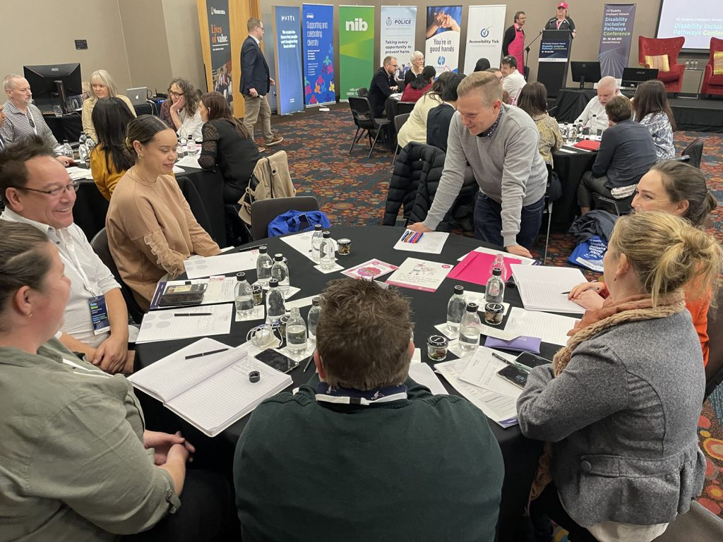 A table of conference delegates engaged in discussion around the Accessibility Game