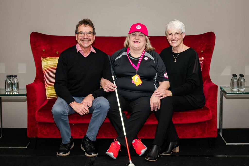 Selwyn Cook, Julie Woods and Sandra Budd sitting on a red couch. They are smiling.