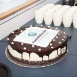 A beautifiul chocolate cake with the Accessibility Tick logo on the front.