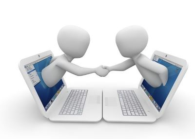 Two animated people reaching out of laptop screens and shaking hands