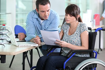 A lady in a wheelchair talks over a document with colleague